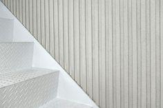 "Store interior design for the fashion designer Julien David. materials : floor: concrete, white paint wall: grooved plaster furniture: vibrated aluminum, cellular concrete block, glass plant: Cyperus alternifolius ""papyrus"" lighting: Filex directional LED spot, fluorescent tube"