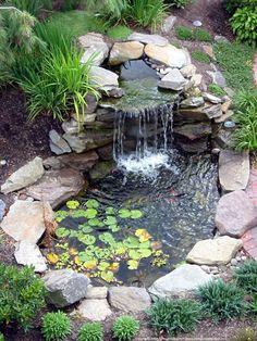 Une cascade d'eau dans un bassin de jardin parfaitement intégré à la nature. (1520×2026)