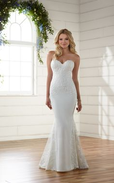 A unique update to a classic silhouette, this sexy, embroidered wedding dress from Essense of Australia is sure to be a head turner! The chic, crepe fabric hugs the body before extending out into a fit and flare silhouette. Its lace appliques are applied throughout the bodice and sweetheart neckline through the train. It's sheer back and layered-lace train create a dramatic look, perfect for making a statement down the aisle. The back zips up beneath fabric buttons.