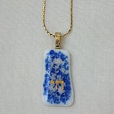 A blue and white beauty that will appeal to any style –conscious Jewish young lady. The contemporary design of this shining glass necklace features a shimmering golden chai set on an elegant and modern looking background of gleaming white glass which is enhanced with a singular swirl of blue. Glass Necklace, Pendant Necklace, Jewish Jewelry, Stainless Steel Necklace, Hamsa, Glass Pendants, Chai, Contemporary Design, Fashion Jewelry