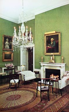 An Adams style handmade English Axminster Rug* in shades of brown, gold and tan with red, blue and white accents. This Axminster rug was chosen for the Green Room of the White House during the Kennedy refurbishing.. This picture was taken in 1963. Even though there is no green in the Axminster rug it is an inspired choice with the fresh green wallcovering.