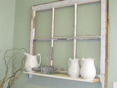 Old & well worn window with shelf added on and hung on wall. Displays my collection of vintage milk spouts