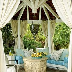 This gazebo in St. Bart's is outfitted with a plush banquette for ample shaded seating. Exposed wood and heavy curtains make the space feel cool and inviting. Coastalliving.com