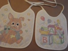 This is a set of 2 baby bibs to cross-stitch and embroider, a bunny and a clown.   These are New, still have stickers on the back, but not in original package.   No directions, but these are stamped in color and really self-explanatory.  These are 50% polyester and 50% cotton, polyester batting, quilted and stamped.Machine washable. Would be a cute baby shower gift.  Excellent condition, no flaws. Each bib measures 10 inches long (not counting the ties) and 9  inches wide.  Ask questions…