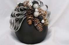 Black ornament decorated with pine cones and miniature ornaments