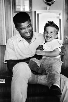 """Ali with the photographer's son Corey in Lewiston, Maine, 1965  -  Bob Gomel: """"Ali has two personas — one public, one private. With my wife, two boys and our German shepherd in tow, I covered the preparation for his rematch with Sonny Liston in Lewiston, Maine, for LIFE magazine. Ali could not have been more solicitous and caring. He and his brother Rahaman kept a kosher Muslim kitchen at Jack Paar's hotel and provided sterilization of the reusable milk-bottle nipples for our youngest son Barry. The braggadocio and histrionics were strictly for show. The Ali we knew was a considerate and warmhearted man.""""   Bob Gomel is a former LIFE magazine photographer."""