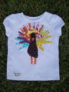 Turkey handprint T- All you need is a tshirt, fabric, iron, Heat N Bond ultra, buttons& thread (eyes), ric rac(legs)  -iron heat n bond on to back of fabric  -trace you childs hand prints and 1 foot print  -arrange however you see fit  -Carefully iron on (easiest to set iron on and press that way)  - iron on beack  -sew on buttons, ribbon, & ric rac    and VOILA!   - HAND WASH ONLY if you plan on not sewing each piece down.     HAPPY CRAFTING!!!  -Charlotte @ Carleigh Bug's