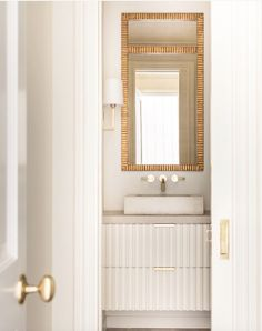 White bathroom | Coats Homes created a glamorous space in a collaboration with architecture firm Pfeffer Torode and interior design by Anne Williams. The neutral palette, wonderful textures, and warm accents make the powder room feel both soothing and sumptuous