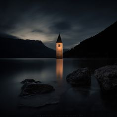 A dark night of werewolfes and vampires...  This is the Reschensee lago di Resia in SouthTirol Italy with his famous under-water-church. The tower is illuminated from the shore. This gives an additional mysterious mood. Martin Pfister