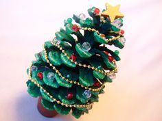 Another version of a pinecone christmas tree. I'll experiment at home before we make these with the senior citizens. Because they are adults, we like to provide sophisticated-looking but easy-to-assemble crafts. The beads might be a bit more grown-up th Christmas Tree Sale, Pine Cone Christmas Tree, Green Christmas, Christmas Crafts For Kids, Christmas Art, Christmas Projects, Christmas Tree Decorations, Holiday Crafts, Pine Tree