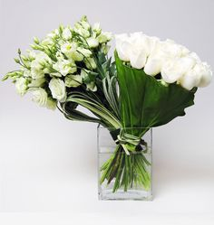 A Duet in White -  A beautiful duet of hand tied bouquets. The elegant South American white roses and fresh lisianthus from Holland are the best of both worlds   L'Olivier Floral Atelier
