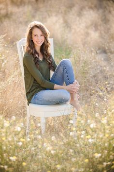 High School Senior girl sitting on a chair in a field of flowers ©Fabiana Beatriz Photography