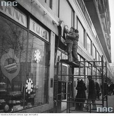 """Sklep """" Sam 1001"""" przy ul. Świętokrzyskiej w Warszawie. Widoczni mężczyźnie montujący neon, 1967 - 1973"""