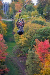 A woman ziplining in the fall