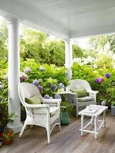 COCOCOZY: 9 PRETTY PORCHES - Love the beautiufl purple and pink hydrangea surrounding this covered porch with white wicker furniture. So sweet. Home Porch, House With Porch, Cottage Porch, Cottage Style, Outdoor Rooms, Outdoor Living, Outdoor Decor, Outdoor Patios, Outdoor Privacy