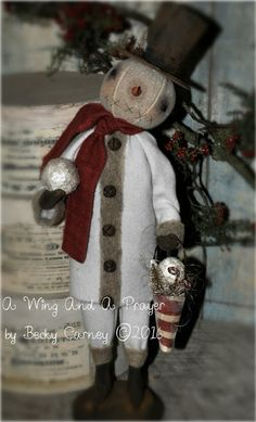 """Earlywork- A Wing and a Prayer - He's a Dapper little Fella, one of my Favorite Snow Guyz... mounted on a primitive wood base he measures 17.5"""" Tall to the top of his hat. He has all hand stitched facial features, with handmade clay eyes, and a curly Carrot nose. His head and arms are wired for limited posing and he has painted on gloves and boots. He is dressed in Dirty White Felted coat & pants trimmed with felted wool roving and rusty bells and felted wool scarf. $129.00 free USA shp SOLD…"""
