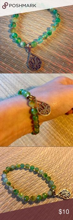 Beaded Bracelet from Bali with Lotus Charm Beautiful beaded bracelet that stretches to fit over your wrist with emerald and jade colored beads and lotus charm. Bought in Bali, never worn! Sorry, no trades. Jewelry Bracelets