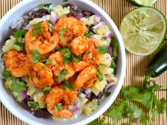Taste the tropics with these easy chili lime shrimp bowls. Rice, black beans, pineapple salsa, and spicy shrimp make a delicious and filling meal in a bowl.