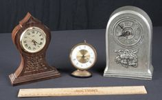 LOT OF VINTAGE CLOCKS INCLUDES A BRASS ON STONE BASE SWIZA-SHEFFIELD ALARM CLOCK (MISSING FINIAL), A SIWA DESK CLOCK WITH CARVED WOOD CASE AND METAL INLAY (TOP INLAY MISSING) AND A 7 INCH ALUMINUM CLOCK WITH FRUIT MOTIF AND NUMEROUS MAKERS MARKS INCLUDING THE YEAR 1774.