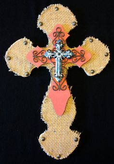 """Medium wooden, quadruple layer, wall cross. The middle cross is painted with red acrylic paint, while the back cross is covered in burlap and accented with decorative upholstery tacks. The piece is then topped with a miniature iron cross and then a blue ceramic cross. Dimensions are approximately 11"""" x 16"""". Each cross is handmade with love and truly one of a kind."""