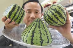 Mototaka Nishimura of the Shibuya Nishimura luxury fruit shop shows off watermelons grown in cubes, pyramids and hearts, at the company's main store in Tokyo on July 1.