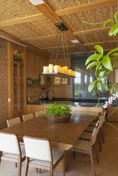Assim como a varanda, o espaço gourmet segue a proposta de decoração rústica com elementos naturais. O ambiente tem churrasqueira, bancada, cristaleira e uma extensa mesa de madeira. O painel de velas led dá um clima aconchegante ao local.
