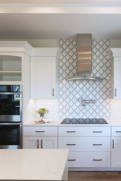 This counter to ceiling tile behind the range gives this induction range and high-end hood a feature look. Kitchen Tile, Kitchen Cabinets, Kitchen Vent Hood, Arabesque Tile, Kitchen Remodel, Kitchen Renovations, Grey Backsplash, Decorative Tile, House In The Woods