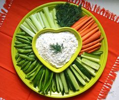 "A veggie tray with dill dip using the Fiesta® 15"" Baking Tray (or the 12"" Baking Tray, depending on the amount of guests) holds an array of freshly cut veggies. In the center place the Fiesta® Medium Heart Bowl filled with dill dip 
