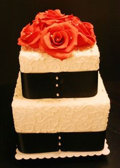 2-tiered square wedding cake with ribbons and piped curlicue details