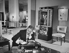 Raymond Loewy designs: 1948: Raymond Loewy rests on a Studebaker model in his home