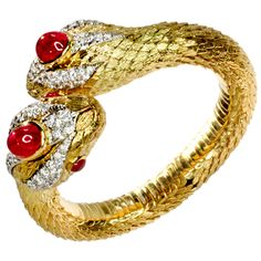 """DAVID WEBB serpent bracelet in 18k yellow gold. Double headed snake cross over bangle or clamper bracelet crowned with large cabochon rubies and smaller cabochon ruby eyes. Heads identically embellished with rows of diamonds. Bodies completely textured in scales and featuring flexible hinge. Signed """"Webb"""" for DAVID WEBB."""