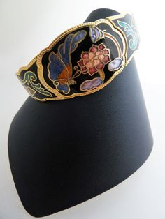 Pretty cloisonné clamper bracelet in gold tone with a design of flowers in red, blue pink and violet and a blue and orange butterflies on a