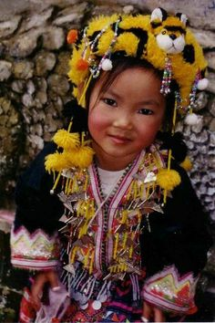 Thailand Chiang Mai small hilltribes girl is part of children Face Earth - This sweet little girl dressed in a hilltribes costume plays around doi Suthep temple, Chiang Mai, she is happy to pose for a small price, Thailand 2006