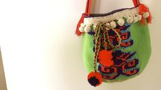 Green Wayuu Bag  Handmade by wayuu women in Venezuela  Its striking pistachio or apple green makes a cool and relaxed style, balanced by the bright orange and its beautiful cream tassels. The blue and orange beading accents the lines on the bag. Although it is a very modern model, the balls in their closure strip maintain the Wayuu essence. By using this bag you will be carrying with you not only a unique design and quality bag, but also history.  This bag can be yours…