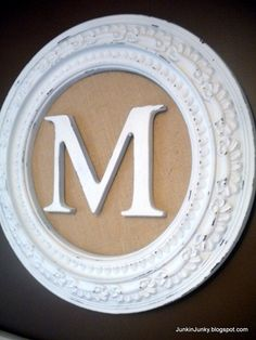 What I think its made of: Molding that's for going around a ceiling fixture, muslin to cover a plywood or cardboard circle and a wooden M! I can so do this! :)