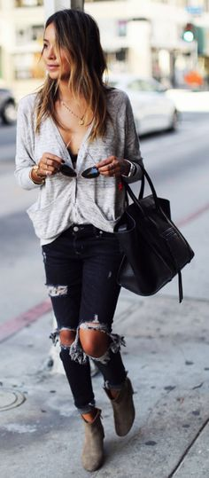 These dark denim jeans are the epitome of distressed! Julie Sarinana rocks this edgy style, wearing the heavily ripped denim with a simple knit cardigan and leather boots; overall a very authentic look.   Cardigan: Zara, Jeans: Lovers & Friends, Boots: Isabel Marant.