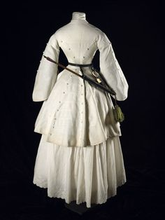 "Museum of London. ""A back view of a three quarter length white cotton Marcella archery jacket with pagoda sleeves, trimmed in military style with braid and covered conical buttons. Fanny Giveen the wife of Captain Xavier Giveen. 1850s Fashion, Victorian Fashion, Vintage Fashion, Retro Mode, Vintage Mode, Vintage Outfits, Vintage Dresses, Historical Costume, Historical Clothing"