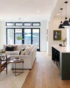 Beautiful open layout concept living room and kitchen with neutral furniture natural white oak wood flooring, black windows, dark island. Love. #openconcept #blackwindows #whiteoak #openlayout