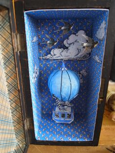 We love making one off hot air balloon diorama box pieces and reuse old wine bowes, tea boxes, cigar boxes and tins in all shapes and sizes. Shadow Box Kunst, Shadow Box Art, Altered Tins, Altered Art, Paper Art, Paper Crafts, Toy Theatre, Tea Box, Assemblage Art
