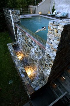 This pool has a sheet of water that cascades 10 feet down. The dramatic wall is made of Oklahoma Chief Cliff stone, and a remote control adjusts the color of the lights in the catch basin as well as the flow of water and its resulting sound.