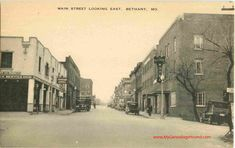 A vintage postcard of Main Street Looking East, Bethany, Missouri. At left is a Standard Service Station. At right is the Gilson Hotel. This postcard view is from about the 1930's. Bethany is in Harrison County, Missouri. Historic Photo