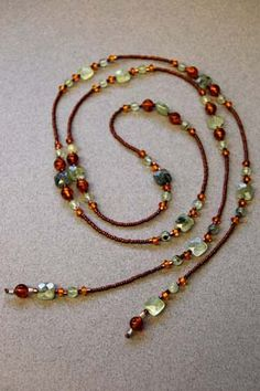 "Lariat  49"" Lariat necklace of green rutilated quartz/amber and copper-colored seed and hex beads. Can be worn long, short or as a bracelet"