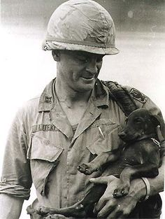 Father Angelo Liteky of the Army's 199th LIB [Light infantry brigade] cradles a four legged friend