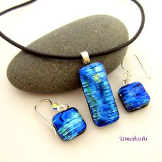 "This is a beautiful pendant and dangle earrings jewelry set made of dichroic fused glass.   The color is a fabulous Caribbean ocean blue that looks like blue fire as the light moves across it.   If there could be ""blue fire"", this would be it! There is a soft blue glow in these pieces of dichroic glass. The blue cabochons display shading from cobalt blue to sky blue with hints of green and gold! There is a striated pattern that runs horizontally across the cabochons.  It is fully capped to…"