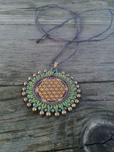 Das Makramemandala wurde um den Blume des Lebens (Flower of Life) Anhänger geknüpft. Die Farben sind ein schönes lila, grün und türkis. Die kleinen Bronzeperlen runden das Design ab und machen die...