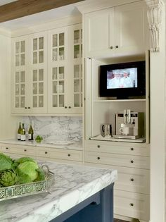Glass front ivory kitchen cabinets are mounted above ivory shaker cabinets topped with a gray and white marble countertop placed against a matching backsplash and beside pull out shelves holding a TV and a coffee maker positioned beneath ivory cabinets.