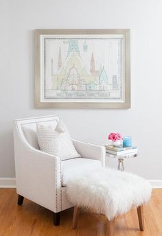 Living room reading corner boasts a white swoop arm chair accented with silver nailhead trim paired with a sheepskin stool and an aluminum wine table placed under a Moroccan blueprint.