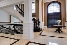 entrance with black detailing on floors and wrought iron staircase Wrought Iron Staircase, Real Estate Auction, Home Theater Design, Photography Gallery, Luxury Interior Design, My Dream Home, Dream Homes, Luxury Living, Beautiful Homes