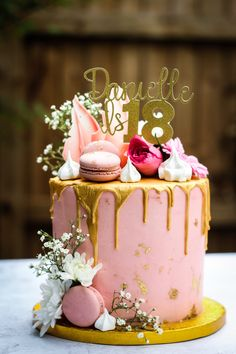 Stunning pink buttercream vanilla cake with a white chocolate gold drip finished with pale pink macaroons, meringue kisses, and fresh flowers such as roses and gypsophilia. There are chocolate shards coloured pink and  this is just the perfect birthday or celebration cake!
