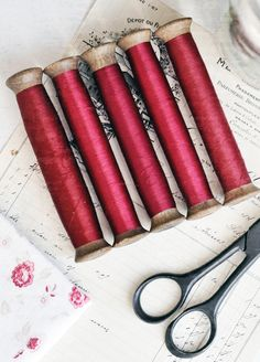 Vintage wooden spools with red thread from a Paris passementerie atelier.